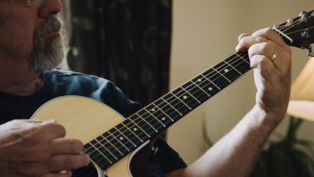 ein kaukasischer mann in seinen 50er jahren spielt eine akustische gitarre in einem wohnzimmer - in den fünfzigern stock-videos und b-roll-filmmaterial