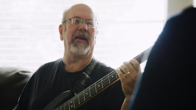 a caucasian man in his fifties plays his five-string electric bass guitar with another person in a domestic living room during the day - bass guitar stock videos & royalty-free footage