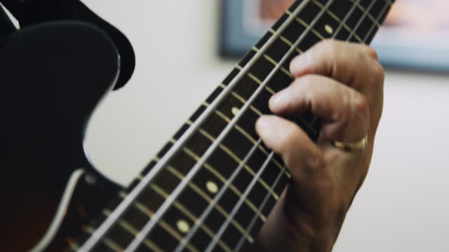 a caucasian man in his fifties presses down on the fretboard of a five-string electric bass guitar while playing music indoors - fretboard stock videos & royalty-free footage