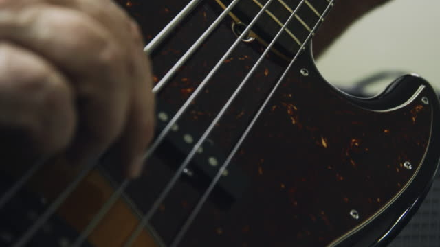 a caucasian man in his fifties presses down on the fretboard of a five-string electric bass guitar and plucks the strings while playing music indoors - fretboard stock videos & royalty-free footage