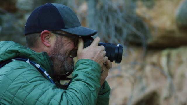a caucasian man in his forties dressed in outdoor gear takes a photo with his slr camera outdoors - digital viewfinder stock videos & royalty-free footage