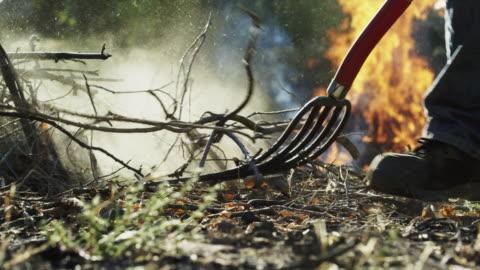 en kaukasisk man i hans fyrtiotalet kastar trä pinnar och grenar på en stor flammande bränna högen med en högaffel utomhus - brinna bildbanksvideor och videomaterial från bakom kulisserna