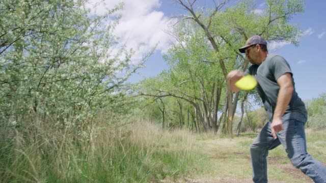 vídeos de stock e filmes b-roll de a caucasian man in his forties uses a backhand drive to throw a disc golf driver a long distance in an uncultivated outdoor area with trees on a sunny day (frisbee golf) - golf