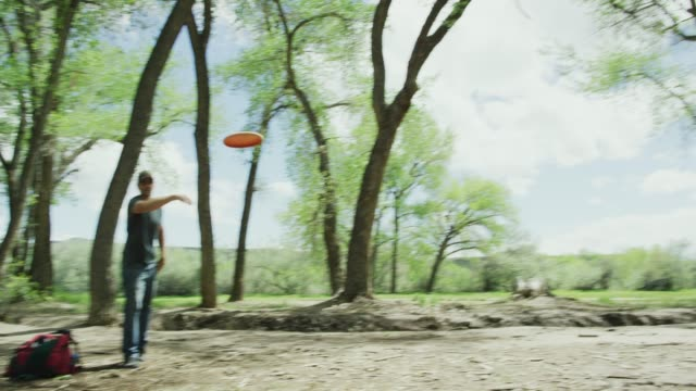 vídeos de stock e filmes b-roll de a caucasian man in his forties uses a backhand putt to throw a disc golf putter into a disc golf basket in an uncultivated outdoor area with trees on a sunny day (frisbee golf) - golf