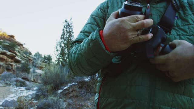 a caucasian man in his forties wearing winter clothing changes the lens on his slr camera while his dog watches in the high desert of western colorado on a winter's day (near the colorado national monument - grand junction, co) - slr camera stock videos and b-roll footage