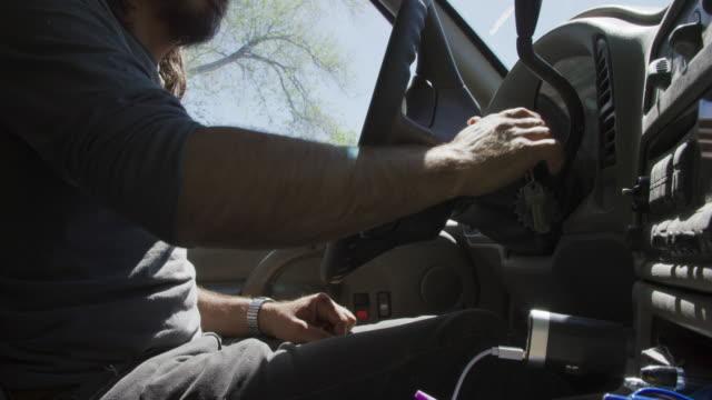 vídeos de stock, filmes e b-roll de um homem caucasiano em seus quarenta anos com uma barba abre sua porta de carro, sobe, coloca a chave na ignição, inicia o carro, coloca em seu cinto de selim, e coloca o carro em marcha em um dia ensolarado. - ignição
