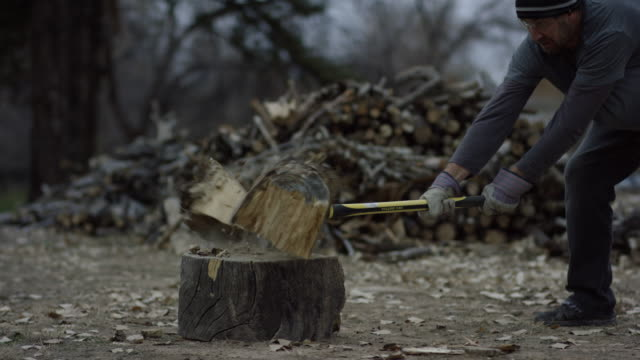 a caucasian man in his forties with a knit hat and safety glasses chops a wooden log in half for firewood with an axe next to a woodpile surrounded by trees outside at dusk on a cloudy day - lumberjack stock videos & royalty-free footage