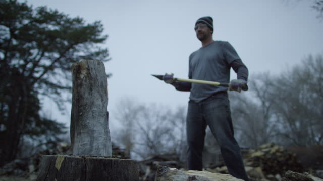 a caucasian man in his forties with a knit hat and safety glasses chops a wooden log in half for firewood with an axe surrounded by trees outside at dusk on a cloudy day - cutting stock videos & royalty-free footage
