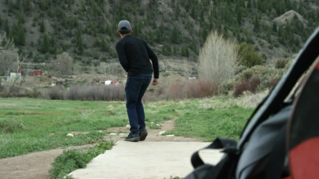 A Caucasian Man in His Thirties Sets Down His Disc Golf Bag and Uses a Forehand Drive to Throw a Disc Golf Driver a Long Distance in a Grassy, Mountainous Landscape