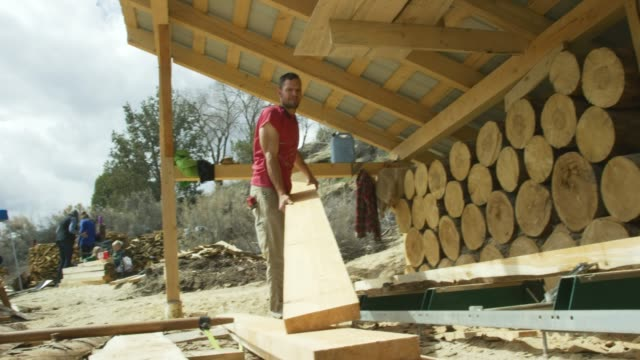 a caucasian man in his thirties stacks wooden planks in an outdoor wood shop next to a large log pile and resets his log milling machine - lumberyard stock videos and b-roll footage