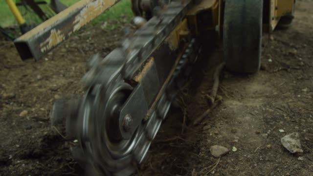 vidéos et rushes de un homme caucasien dans ses années trente commence une trancheuse en tirant sur la corde de traction tout en se préparant à couper une tranchée dans le sol à l'extérieur - corde