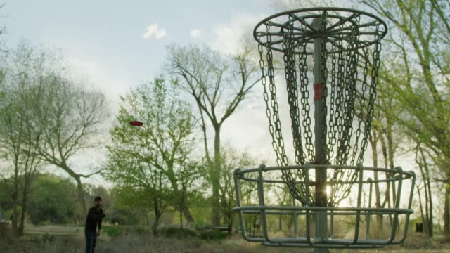 vídeos de stock e filmes b-roll de a caucasian man in his thirties uses a backhand putt to throw a disc golf putter into a disc golf basket in an uncultivated outdoor area at a disc golf course with trees at sunset (frisbee golf) - golf