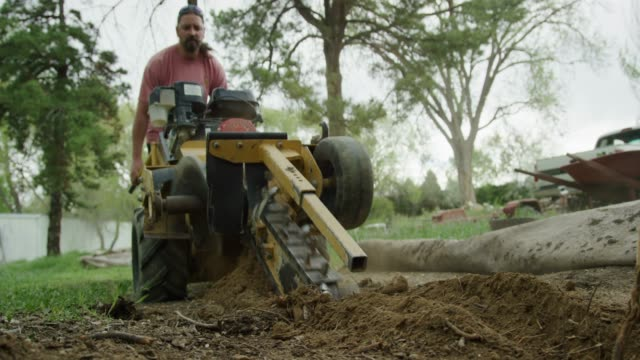 a caucasian man in his thirties uses a trencher to cut a trench in the ground outdoors - trench stock videos & royalty-free footage