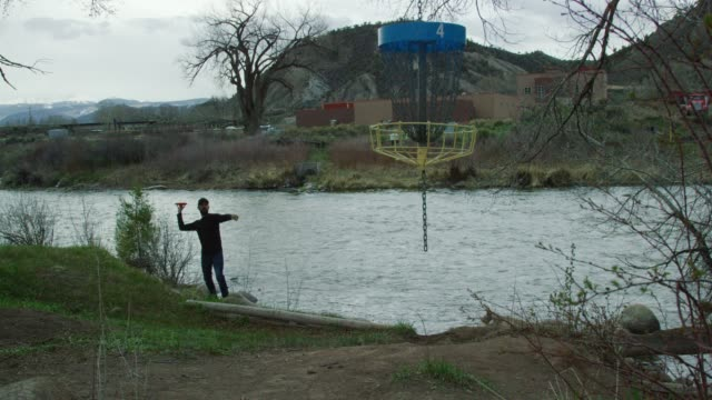 a caucasian man in his thirties uses a turbo putt (aka pizza toss or pie toss) to throw a disc golf putter into a hanging disc golf basket next to a river in a mountainous landscape under storm clouds - holing stock videos & royalty-free footage