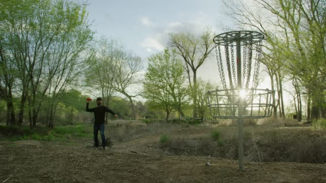 vídeos de stock e filmes b-roll de a caucasian man in his thirties uses a turbo putt (aka pizza toss or pie toss) to throw a disc golf putter into a disc golf basket in an uncultivated outdoor area at a disc golf course with trees at sunset (frisbee golf) - golf
