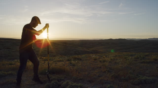 a caucasian man in his thirties wearing a hat digs a hole in the ground with a shovel in the desert at sunset - digging stock videos & royalty-free footage