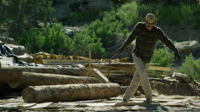 a caucasian man in his thirties wearing protective gloves uses a rope to roll a log towards him in a lumberyard on a sunny day - log stock videos & royalty-free footage