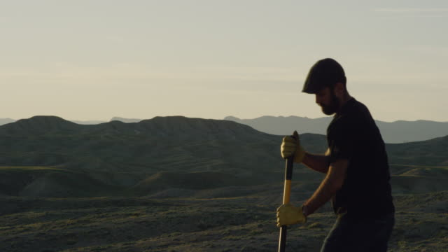 vídeos de stock e filmes b-roll de a caucasian man in his thirties with a beard and wearing a hat and work gloves digs a hole in the ground with a shovel in the desert at sunset - cavar