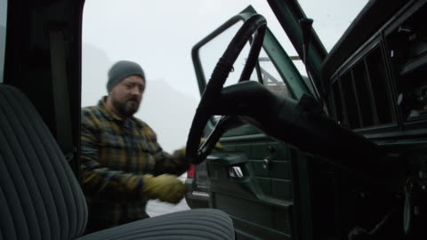 a caucasian man in his thirties with a beard climbs into his truck in the mountains on a snowy winter day - truck stock videos & royalty-free footage