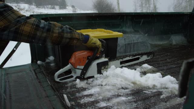 ein kaukasischer mann in seinen dreißigern mit einem bart steigt aus seinem klassischen green truck, öffnet die heckklappe und zieht sich ein motorsäge im wald an einem verschneiten wintertag - heckklappe teil eines fahrzeugs stock-videos und b-roll-filmmaterial