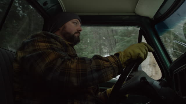 a caucasian man in his thirties with a beard drives his truck in an evergreen forest on a snowy winter day - beard stock videos & royalty-free footage