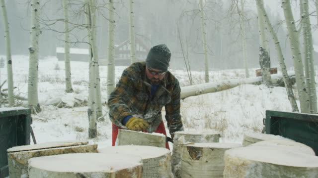 vídeos de stock, filmes e b-roll de um homem caucasiano em seus trinta anos, com uma barba coloca um log de aspen seu caminhão com a sua casa em segundo plano em um dia de inverno a neve nas montanhas. em seguida, ele fecha a porta da bagageira, sobe em seu caminhão e inicia-lo. - tronco parte de planta
