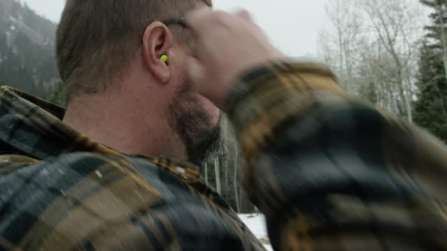 vídeos de stock, filmes e b-roll de um homem caucasiano em seus trinta anos, com uma barba coloca tampões nas orelhas no bosque em um dia de inverno a neve nas montanhas - protetor de ouvido