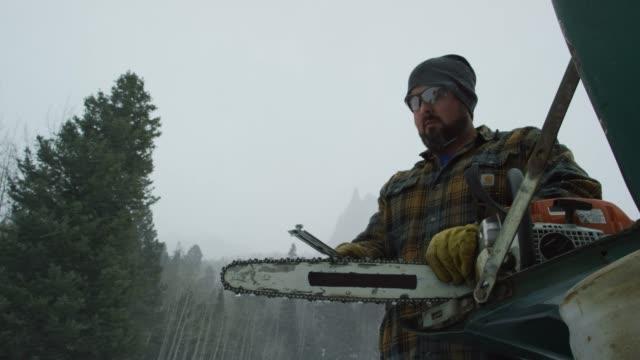 vídeos de stock, filmes e b-roll de um homem caucasiano em seus trinta anos, com uma barba aguça sua motosserra no tailgate do seu caminhão na floresta num dia de inverno a neve nas montanhas (foto) - afiado