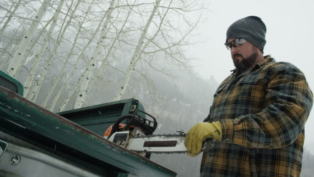 vídeos de stock, filmes e b-roll de um homem caucasiano em seus trinta anos, com uma barba aguça sua motosserra no tailgate do seu caminhão na floresta num dia de inverno a neve nas montanhas (dose média) - afiado