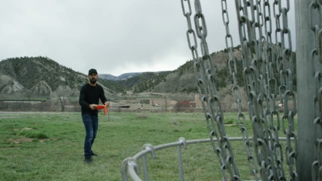 a caucasian man in his thirties with a beard uses a backhand putt to throw a disc golf putter into a disc golf basket in a grassy field at a disc golf course with mountains in the background under storm clouds (frisbee golf) - one mid adult man only stock videos & royalty-free footage