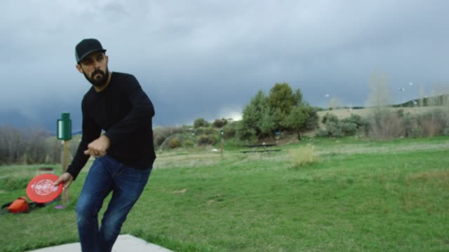 vídeos de stock e filmes b-roll de a caucasian man in his thirties with a beard uses a forehand drive to throw a red disc golf driver across an outdoor area with trees under storm clouds at sunset (frisbee golf) - golf