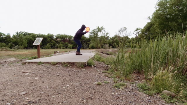 a caucasian man in his thirties with a beard walks up to a disc golf pad and uses a forehand drive to throw an orange disc golf driver across an outdoor area with trees on an overcast day (frisbee golf) - forehand stock videos & royalty-free footage