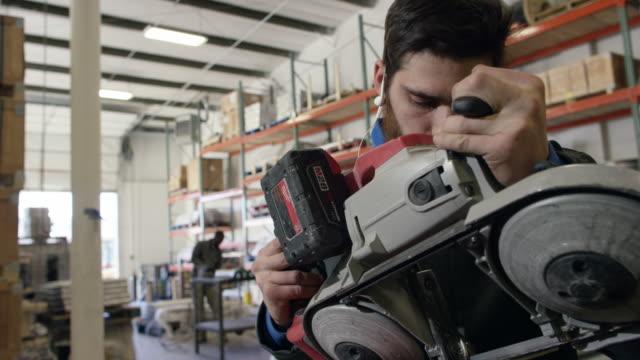 vidéos et rushes de un homme caucasien dans la vingtaine avec une barbe de hauteur, marque et coupe d'un tuyau d'acier avec une scie à ruban portable dans une usine de fabrication - metal