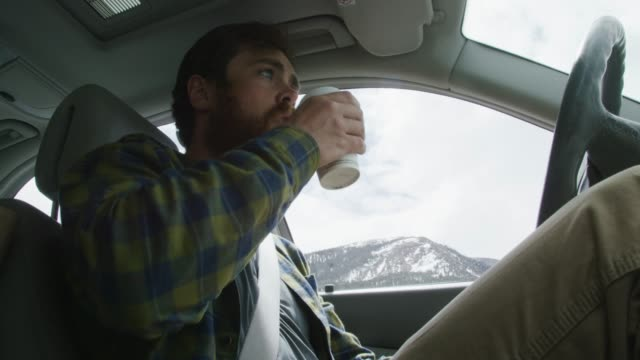 a caucasian man in his twenties with a beard picks up a to-go cup, takes a sip, and sets it back down again in the console while driving through snowcapped mountains in winter - picking up stock videos & royalty-free footage
