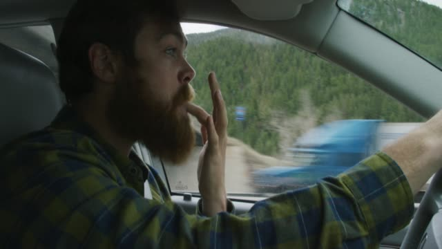 vídeos de stock e filmes b-roll de a caucasian man in his twenties with a beard shoves the rest of a sandwich into his mouth, licks his fingers, and wipes his hands on his bands while driving in the mountains with a forest - estilo de vida pouco saudável