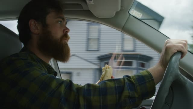 a caucasian man in his twenties with a beard takes bites out of a sandwich while driving through a mountain town on a sunny day - sandwich stock videos & royalty-free footage