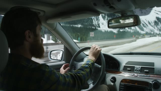 a caucasian man in his twenties with a beard taps on the steering wheel as he drives along interstate 70 in the rocky mountains of colorado under a partly cloudy sky in winter - general view stock videos & royalty-free footage