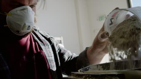 vídeos y material grabado en eventos de stock de hombre caucásico en sus veinte años con un respirador derrama polvo blanco en un recipiente cilíndrico en una planta de fabricación - típico de la clase trabajadora