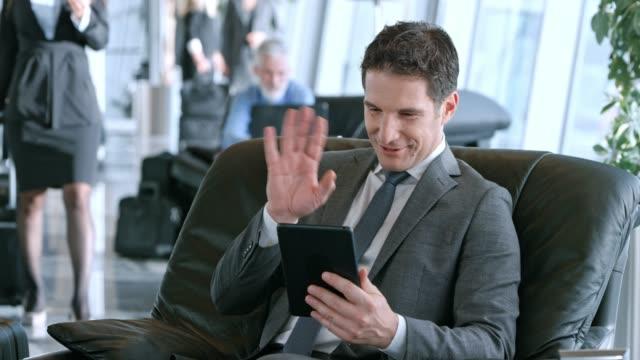 vídeos de stock, filmes e b-roll de homem caucasiano de ds no salão de negócios, mantendo seu tablet e tendo uma chamada de vídeo com sua família - parte de uma série
