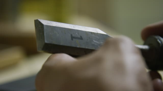 a caucasian man inspects and tests a 1 inch metal chisel for sharpness in an indoor workshop - inch stock videos & royalty-free footage