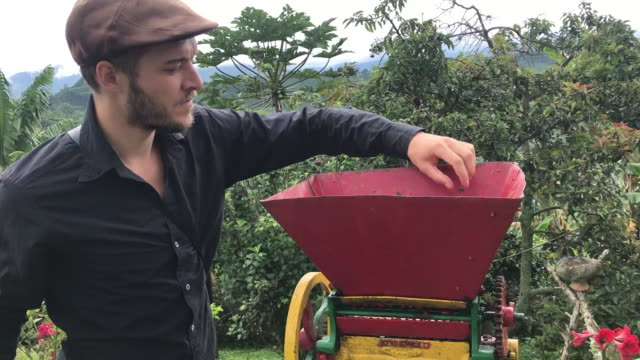 caucasian man is turning over a organic coffee peeling machine in a black bucket in jardín, antioquia / colombia - coffee variation stock videos & royalty-free footage