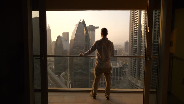 Caucasian man looking at cityscape with high rise buildings form his balcony