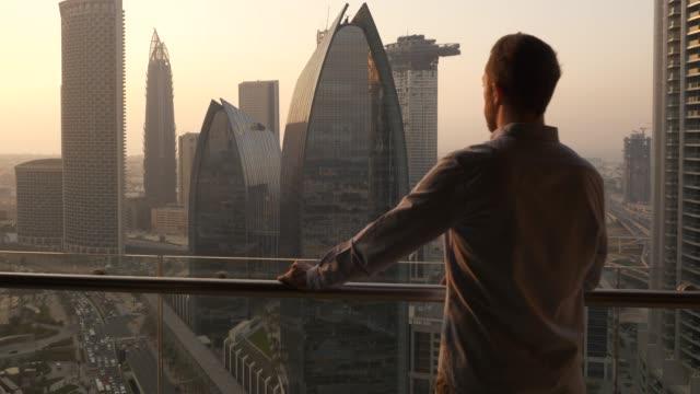 vidéos et rushes de caucasian man looking at cityscape with high rise buildings form his balcony - vie citadine