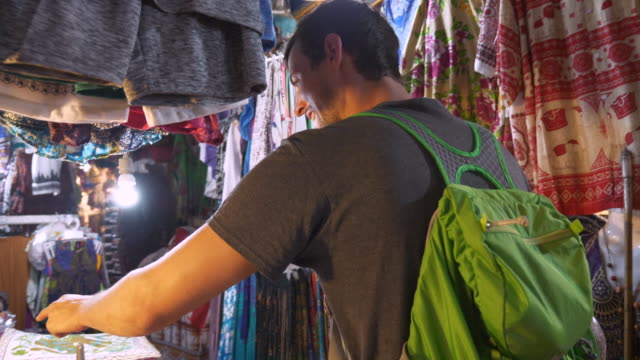 caucasian man looking for souvenirs in cambodian market - craft product stock videos and b-roll footage