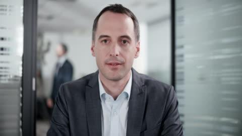 kaukasiska man på ett videosamtal från hans kontor - videokonferens bildbanksvideor och videomaterial från bakom kulisserna