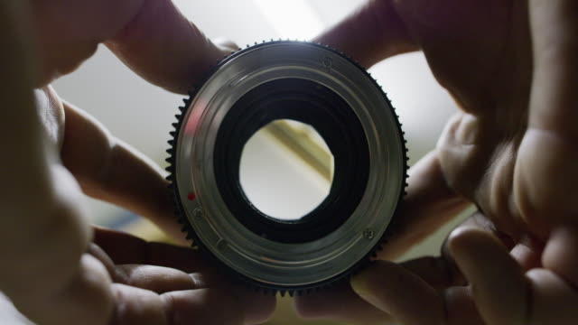 a caucasian man opens and closes a lens aperture - camera photographic equipment stock videos and b-roll footage