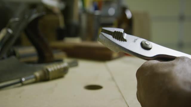 en kaukasisk man öppnar och stänger ett par metall tänkare i en indoor workshop - tång bildbanksvideor och videomaterial från bakom kulisserna