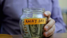 Caucasian man putting a glass jar put in a drawer table with his savings for future rainy day