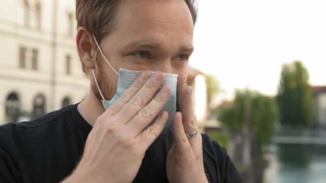 caucasian man putting on face mask in the city - applying stock videos & royalty-free footage