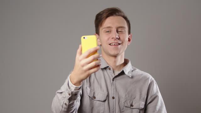 vidéos et rushes de homme caucasien disant salut tout en faisant l'appel vidéo sur le smarphone d'isolement sur le fond gris - acteur